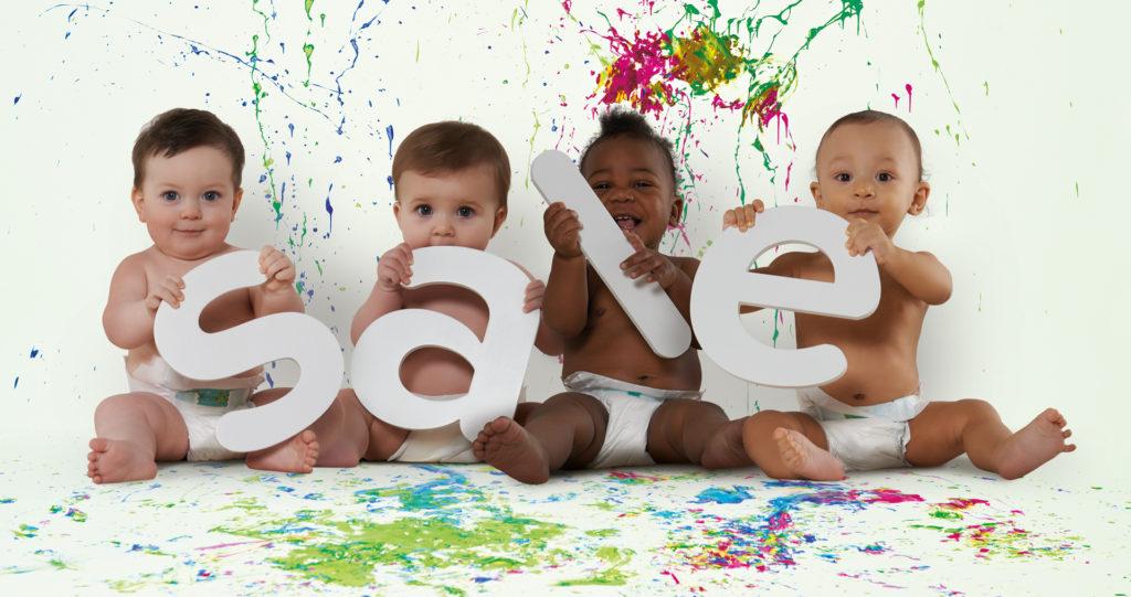 Four babies holding SALE letters